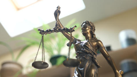 Statue of Themis or Lady Justice on Bookshelf Background Live Action