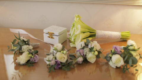 Beautiful wedding bouquets lie on a table near box with wedding rings Live Action