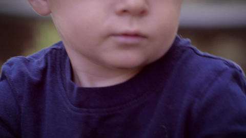 An intimate close up portrait of a young little blond child looking and talking Footage