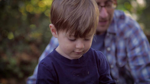 Slow motion rack focus of a father and son playing together while the cute littl Footage