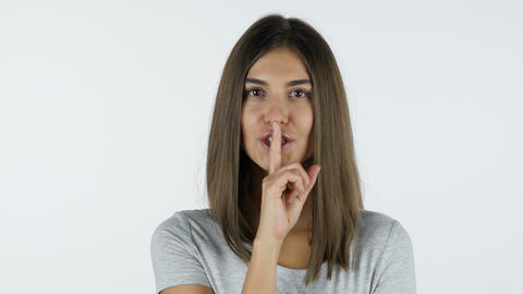 Gesture of silence, Finger on Lips by Beautiful Girl, White Background in Studio Footage