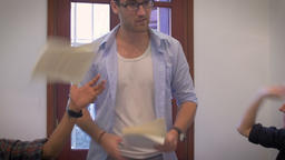 A young man and boss loses control of a meeting while his coworkers throw paper  Footage
