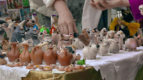 Buyers Consider Souvenirs Hand-Made of Clay in Stall in Open Air Footage