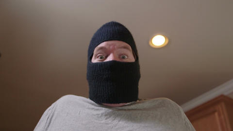 A man in ski mask - a burglar or thief breaking into a house is surprised as he Footage