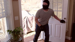 A man who is a thief and burglar breaking into a house through the back door whi Footage