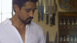 Medium dolly shot of an attractive young latino man in his 30's cooking breakfas Live Action