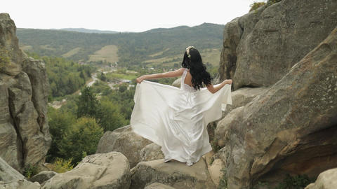 Beautiful and lovely bride standing on the mountain hills. Woman in love Live Action