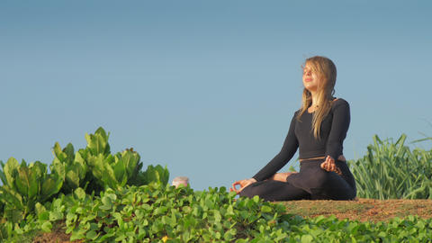 lady with long loose flowing hair meditates in yoga pose Live Action