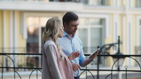 Serious business couple using tablet computer. Business partners talking outdoor Live Action