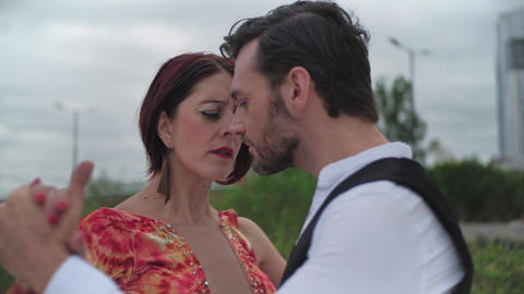 Two handsome tango dancers performing outdoors, looking each other with passion Live Action