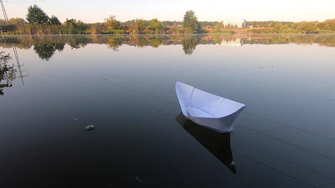 White boat floats on smooth mirror surface of pond lake in calm Live Action