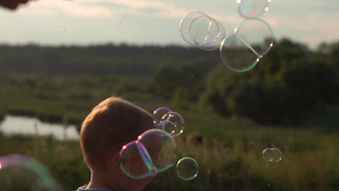 Funny Little boy and soap bubbles at sunset in slow motion. Boy in blue t-shirt Live Action