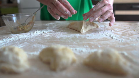 Cook's hands hands make a triangle-shaped pie from the dough, slow motion Live Action