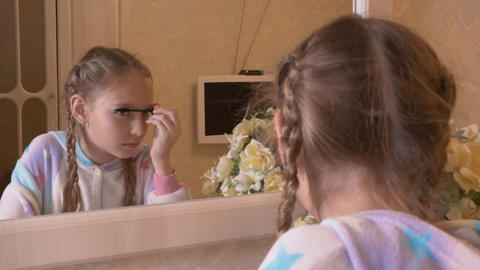 Girl teenager applying mascara on eyelashes front mirror in bedroom. Young girl Live Action