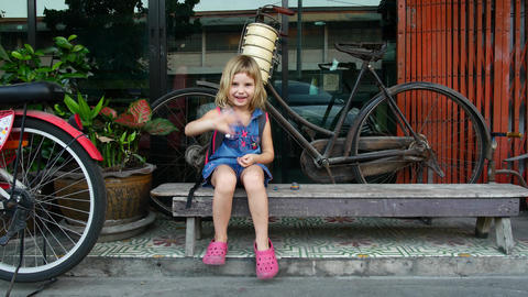 Girl on a bench near the store. The child waves a friendly hand Live Action