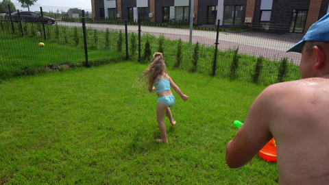 Playful father splashing water at his daughter girl with water gun Live Action