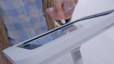 Woman hand using touchscreen display of floor standing white tablet kiosk Live Action