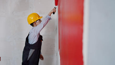 Apartment renovation - a little boy painting wall in red Live Action