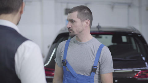 Portrait of young Caucasian auto mechanic talking with customer in repair shop Live Action