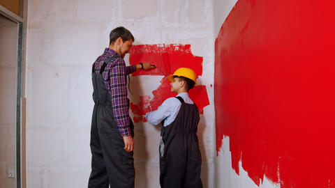 Apartment renovation - family of father and son covering wall in red paint Live Action