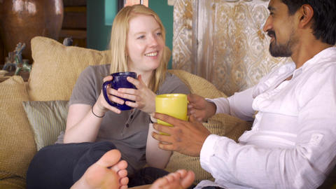 An affectionate mixed racial couple in their 20's drink coffee on a comfortable  Footage