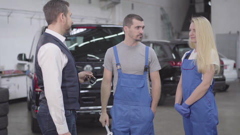 Adult Caucasian businessman giving car keys to auto mechanics standing in repair Live Action