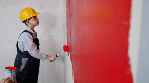 Apartment renovation - a little boy in helmet and glasses painting wall in red Live Action