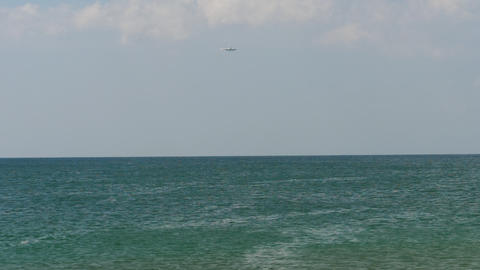 Airplane approaching over ocean GIF