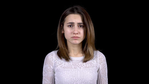 A young woman shows emotions of sadness on her face. The woman is sad on a black Live Action