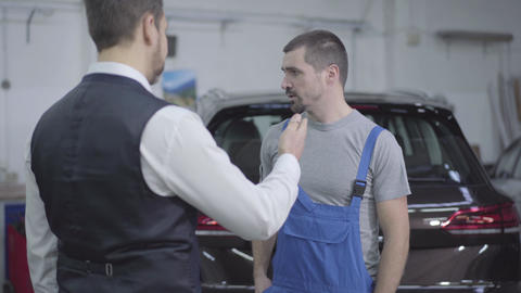 Young Caucasian man in workrobe taking customer's car keys in repair shop and Live Action