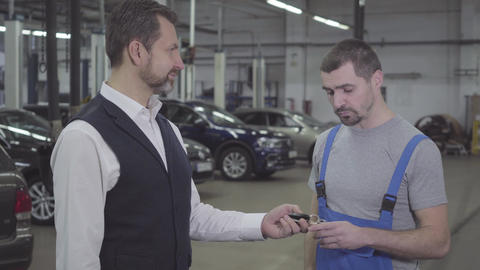 Side view of handsome adult Caucasian man giving car keys to auto mechanic and Live Action