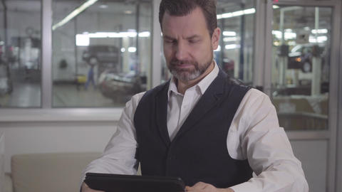 Portrait of young Caucasian male manager of repair shop sitting with tablet at Live Action