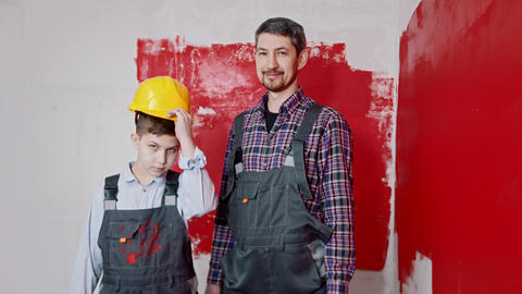 A little boy and his father painting walls - a boy puts on a helmet and holding Live Action