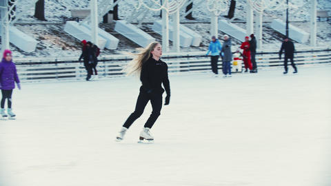 A young blonde woman professional figure skater performing tricks on ice rink Live Action