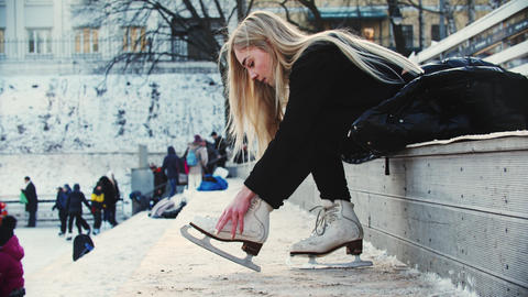 A young woman with blond hair tie up her figure skates before walking out on the Live Action