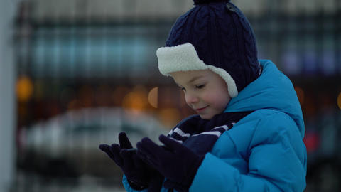 Little boy in winter wear using phone on cold snowy day Live Action