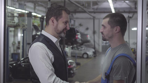 Side view close-up of two Caucasian men shaking hands in repair shop and talking Live Action