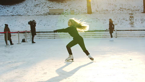 A young blonde woman figure skater spinning around herself on ice rink Live Action