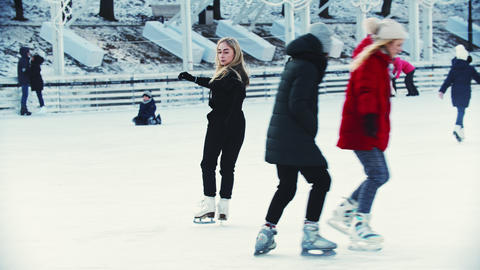 A young blonde woman professional figure skater on the outdoors ice rink Live Action