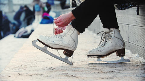 A young blonde woman tie up her figure skates before walking out on the rink Live Action