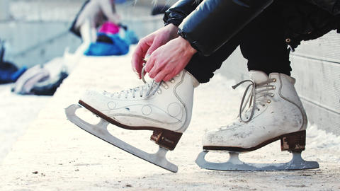 A woman untie her figure skates Live Action