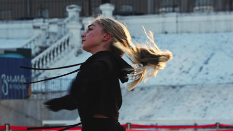 A young woman figure skater spinning around herself on ice rink outdoors Live Action