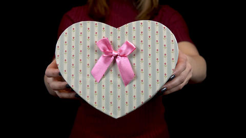 A young woman holds out a heart-shaped box to the camera. Woman holding a gift Live Action