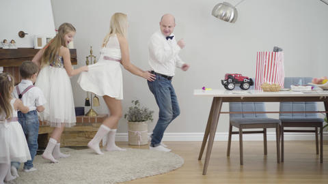Cheerful Caucasian family dancing around table indoors. Smiling father, mother Live Action
