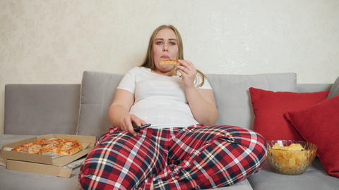 Woman with overweight eating pizza and watching tv Live Action
