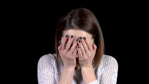 The young woman shows emotions of sadness on her face. Woman cries and covers Live Action