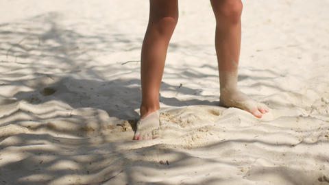 A child is playing in the sand, beach vacation Live Action