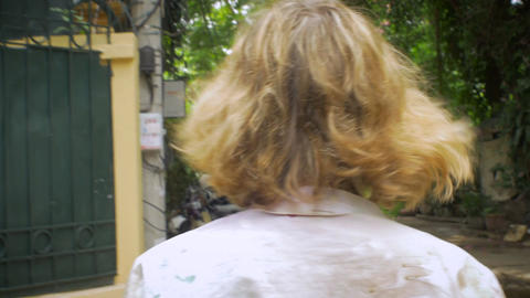Camera follows a young blond woman as she walks into a cafe from behind in a han Footage