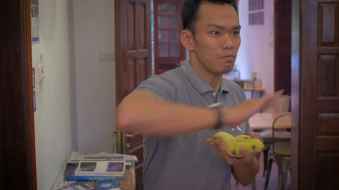 Medium shot of a young Asian man throwing five bananas out of his hand while loo Footage