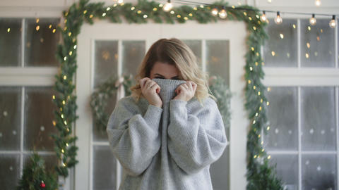 European attractive woman in warm clothes wraps up in a sweater and looks to the Live Action